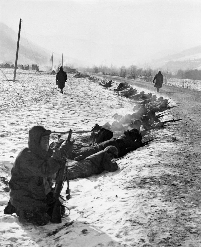 In this photo released by the U.S. Marine Corps, a small detail of U.S. Marines lies in the snow with rifles ready at a curve in a road near Yudan in the Chosin Reservoir area northwest of the port of Hungnam, Korea, Nov. 29, 1950.  They are shown at their snowy post as the 1st and 7th Marine regiments were retiring under heavy pressure by three enemy divisions.  One soldier, right, has a bayonet fixed on his weapon.