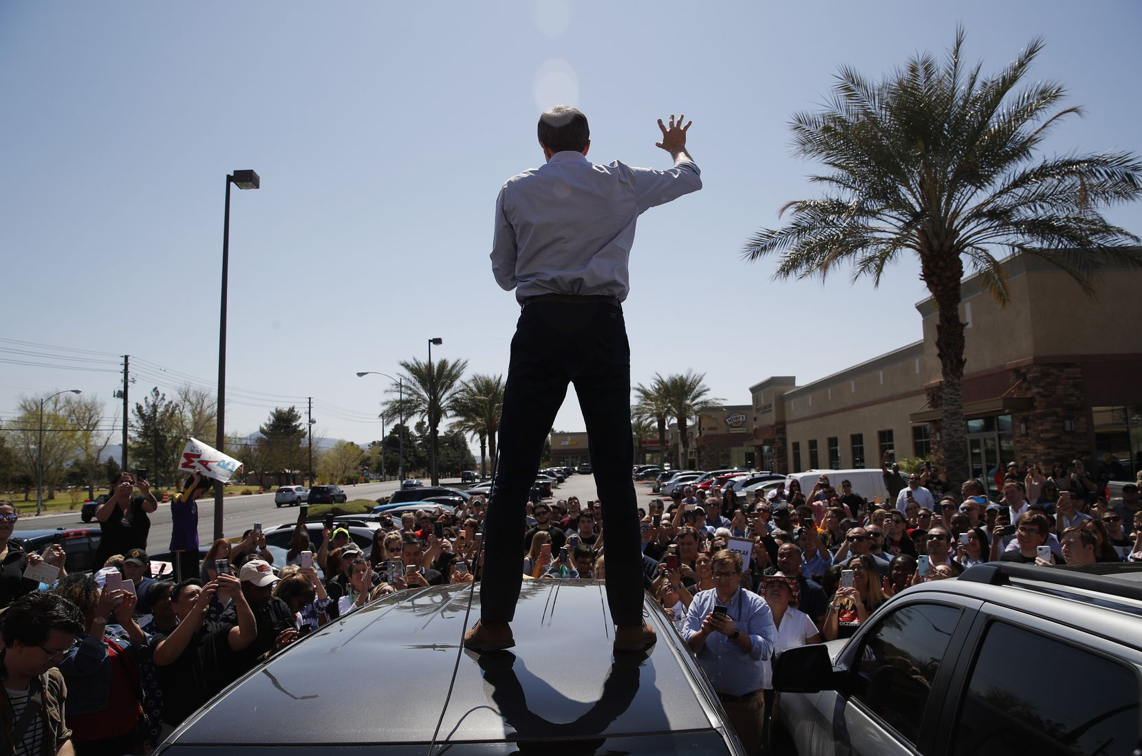 Democratic presidential candidate and former Texas congressman Beto O'Rourke speaks from the roof of his car to an overflow crowd at a campaign stop at a coffee shop Sunday, March 24, 2019, in Las Vegas.