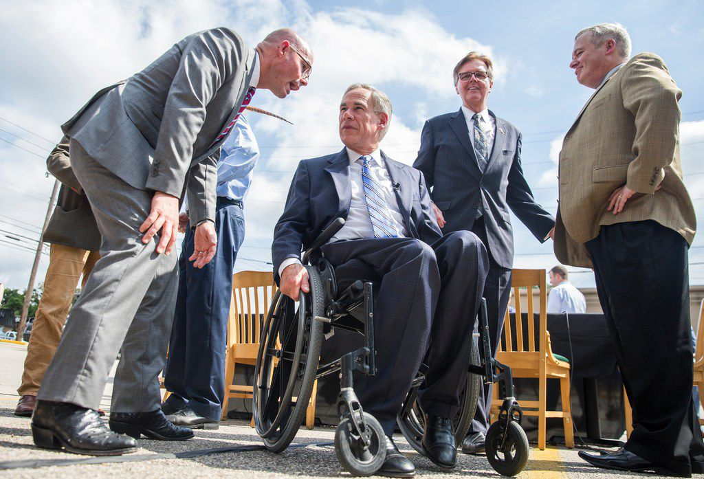 Gov. Greg Abbott listens to Speaker Dennis Bonnen after Abbott signed a bill that limits property tax growth at an Austin restaurant on June 12. The same day, Bonnen and top lieutenant Rep. Dustin Burrows met with conservative activist Michael Quinn Sullivan, who's accused the two House leaders of making an improper quid pro quo offer. Sullivan says he rejected the offer.