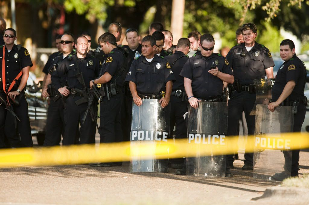 Police with riot gear and assault rifles stand guard to keep spectators away from the scene of an officer involved shooting at Dixon Avenue and Bourquin Street in southeast Dallas on July 24, 2012. (Jeff Lautenberger/The Dallas Morning News)  -- police shooting of James Harper in the Dixon Circle community 08112012xALDIA