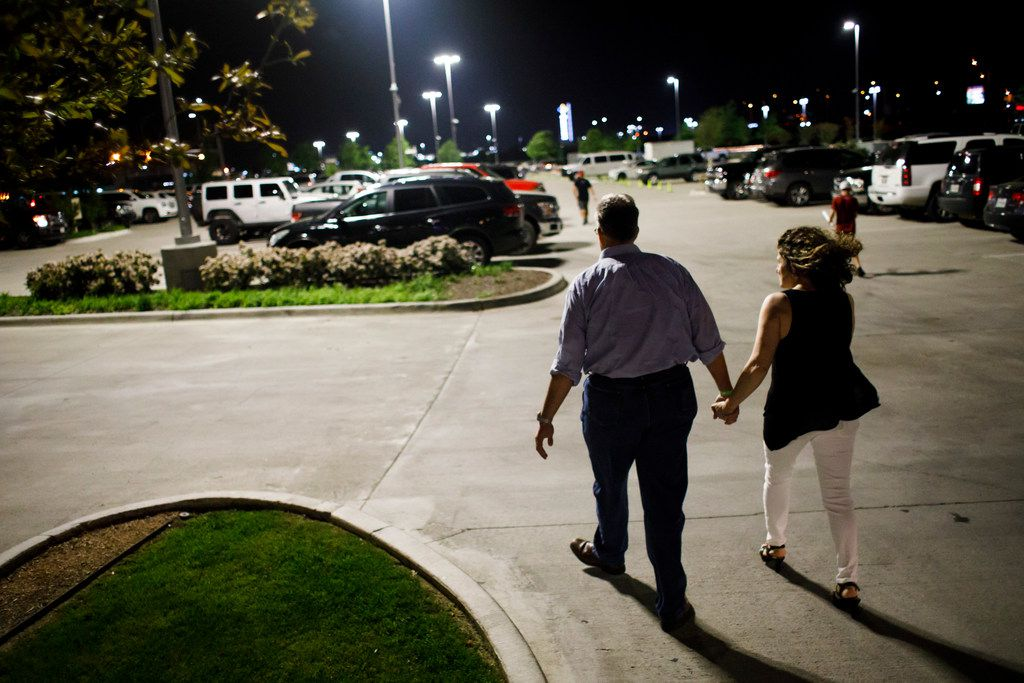 Meryl Evans holds hands with her husband, Paul Evans, as they leave a concert.