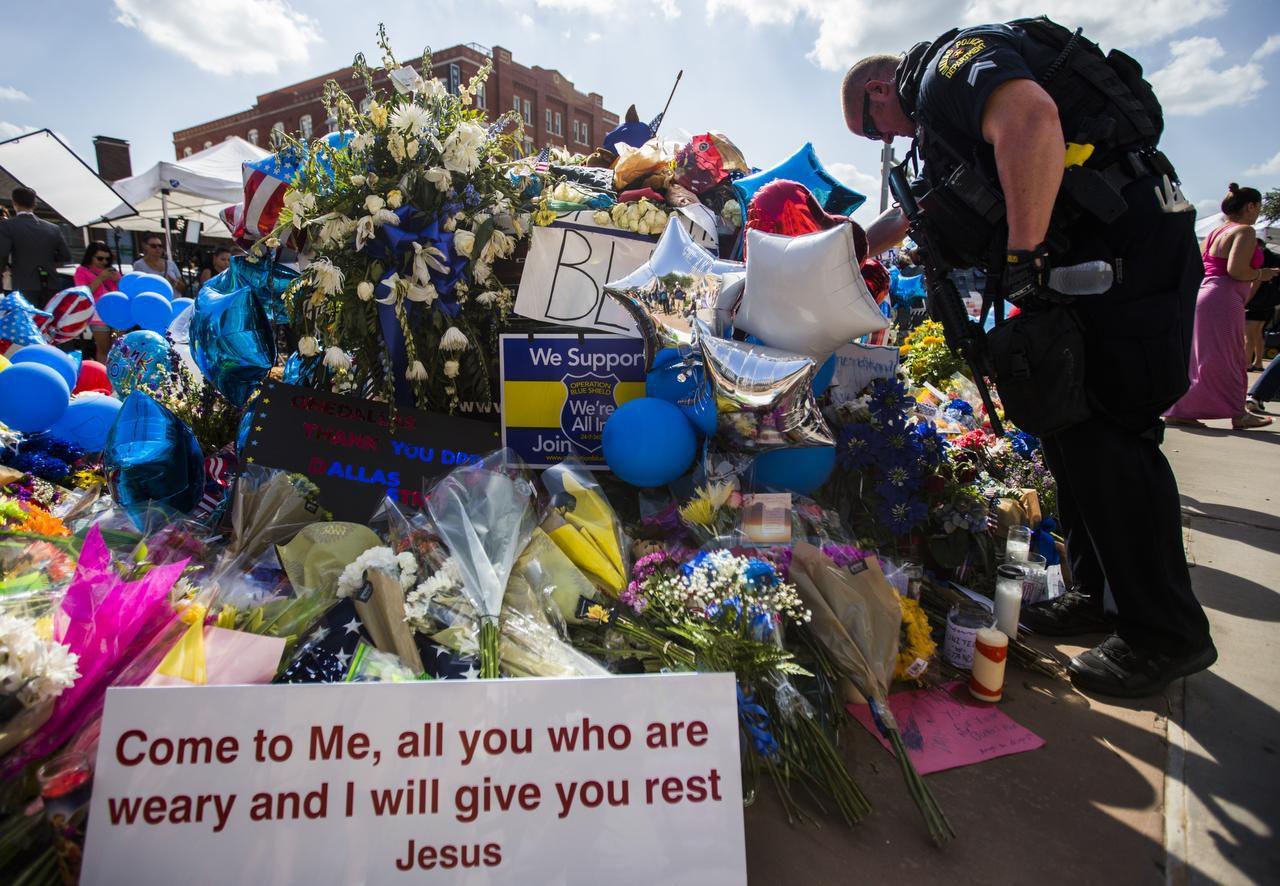 El agente de policía de Dallas Daniel Sullivan contempla una patrulla de policía llena de flores y mensajes de apoyo para los agentes del orden, en el cuartel gederal del Departamento de Policía de Dallas. (DMN/ASHLEY LANDIS)