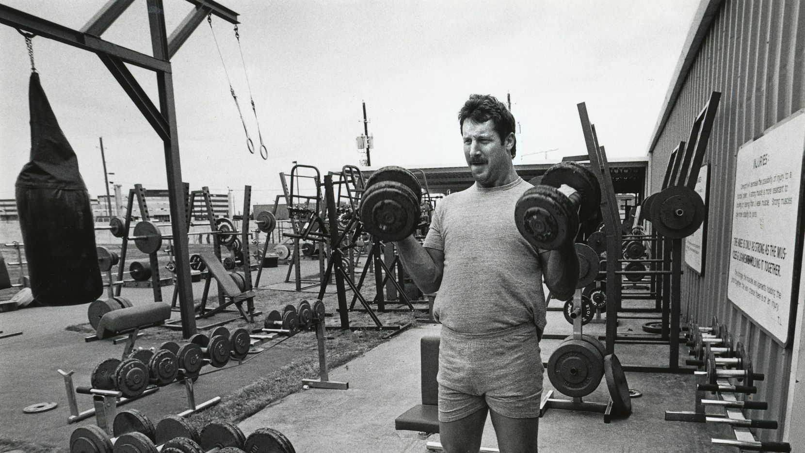 Cowboys defensive lineman Randy White lifts weights at the team's practice facilities at Forest Lane and Abrams. The Cowboys began improving their weight program during this era, primarily lifting outside, under an awning.