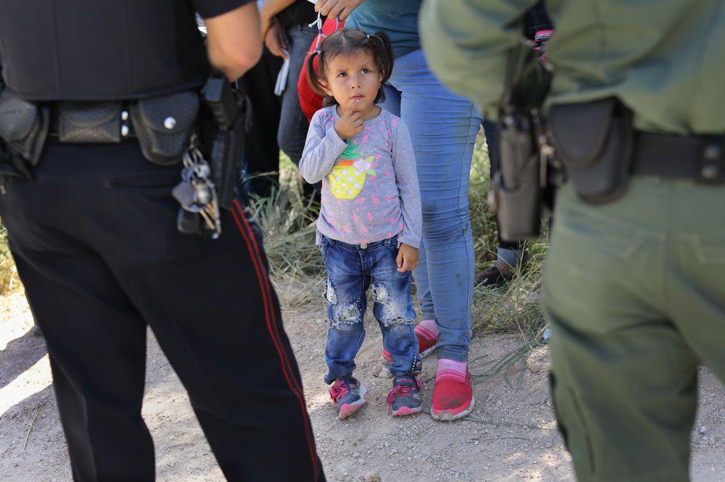 Un oficial del Departamento de Policía de la Misión (L) y un agente de la Patrulla Fronteriza de Estados Unidos vigilan a un grupo de solicitantes de asilo centroamericanos antes de arrestarlos el 12 de junio de 2018 cerca de McAllen, Texas. (Foto de John Moore / Getty Images)