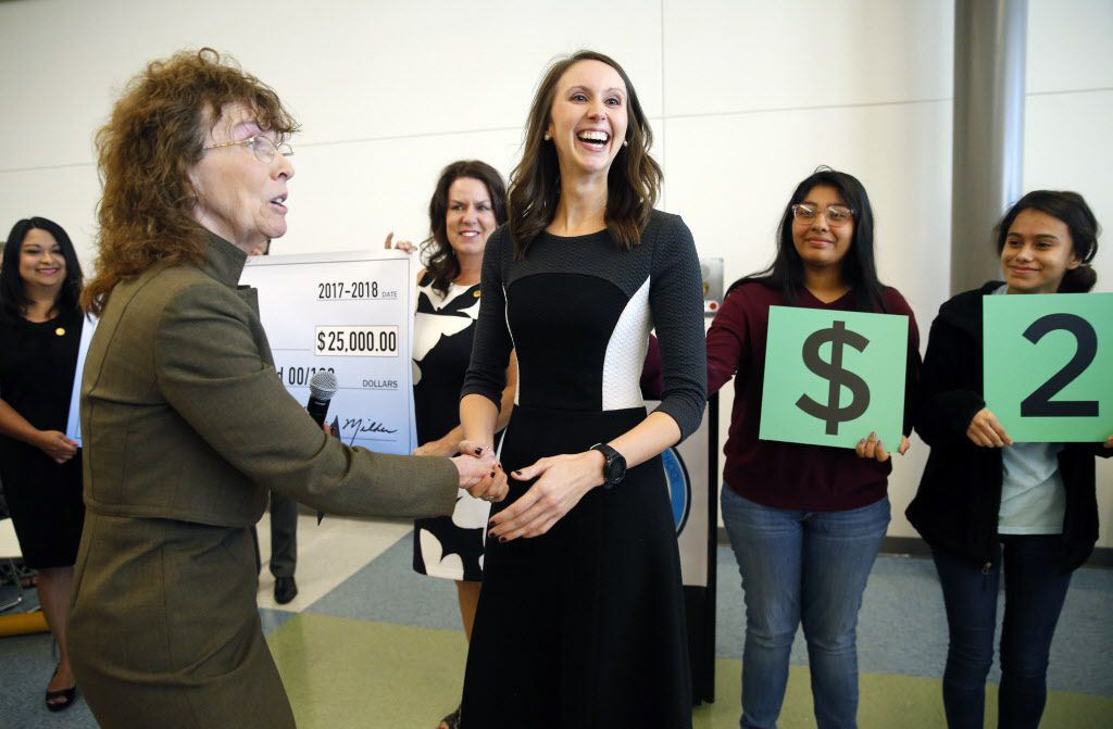 Arlington Collegiate High School teacher Jennifer Fuller (center) is congratulated by Milken Educator Awards senior vice president Jane Foley after receiving the coveted Milken Educator Award, one of two in the state of Texas, during an assembly at the school in Arlington, Texas, Wednesday, October 18, 2017. The award came with a $25,000 check.