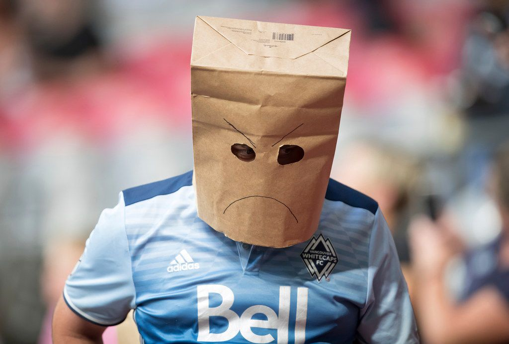 A Vancouver Whitecaps supporter wears a paper bag on his head as the Whitecaps and the San Jose Earthquakes play an MLS soccer match in Vancouver, British Columbia, Saturday July 20, 2019. (Darryl Dyck/The Canadian Press via AP)