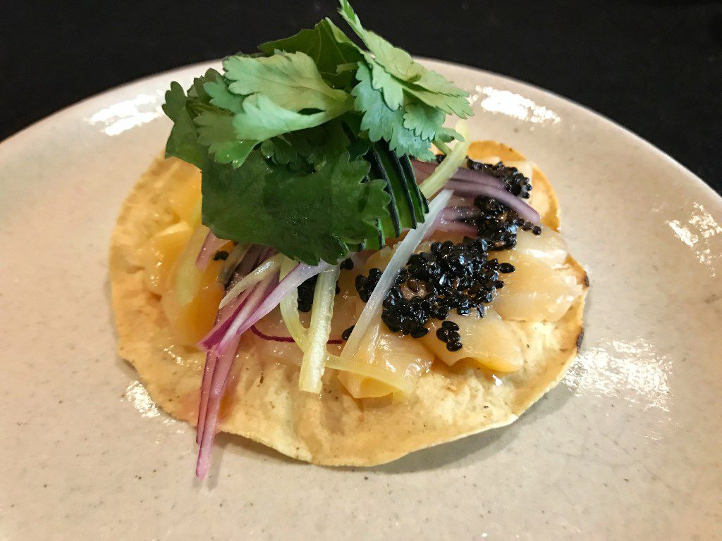 Tostada  de callos -- raw callo espinudo scallops from Ensenada, Baja Mexico. The tostada (or tostadita, perhaps – it's about three inches across) is dressed with thin-sliced avocado, cilantro, slivered red and white onion and a black sesame salsa.