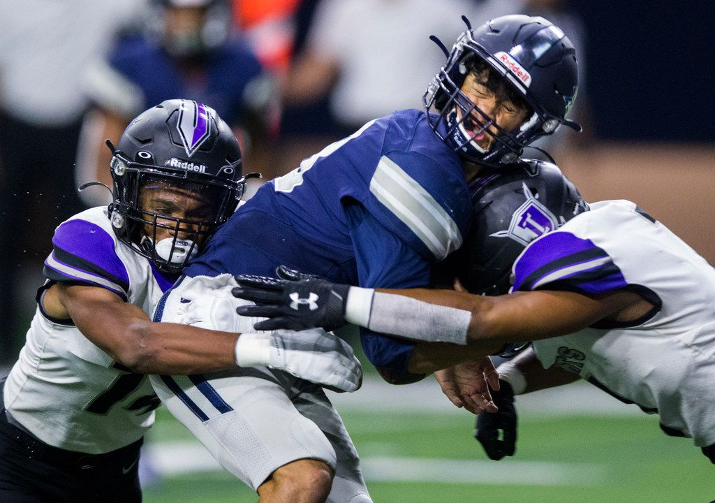 Frisco Lone Star quarterback Garret Rangel (13) is tackled by Frisco Independence defensive backs Caleb Ellis (14) and Princeton Ferguson (7) during the first quarter of a District 5-5A Division I high school football game between Frisco Independence and Frisco Lone Star on Thursday, October 10, 2019 at the Ford Center at The Star in Frisco. (Ashley Landis/The Dallas Morning News)