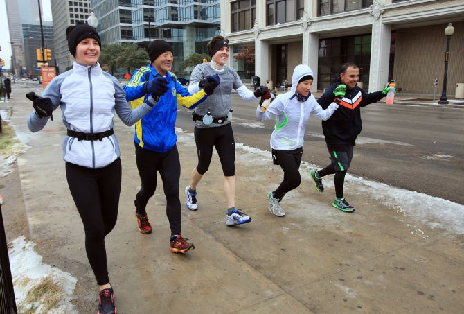 Jonathan Eisenzopf (center), 39, holding hands with other runners including Eunsup Kim (left), 60 and Sarah Johnson, raced to the finish line Sunday on Elm Street in their own version of the Dallas Marathon. The official race was called off because of ice.