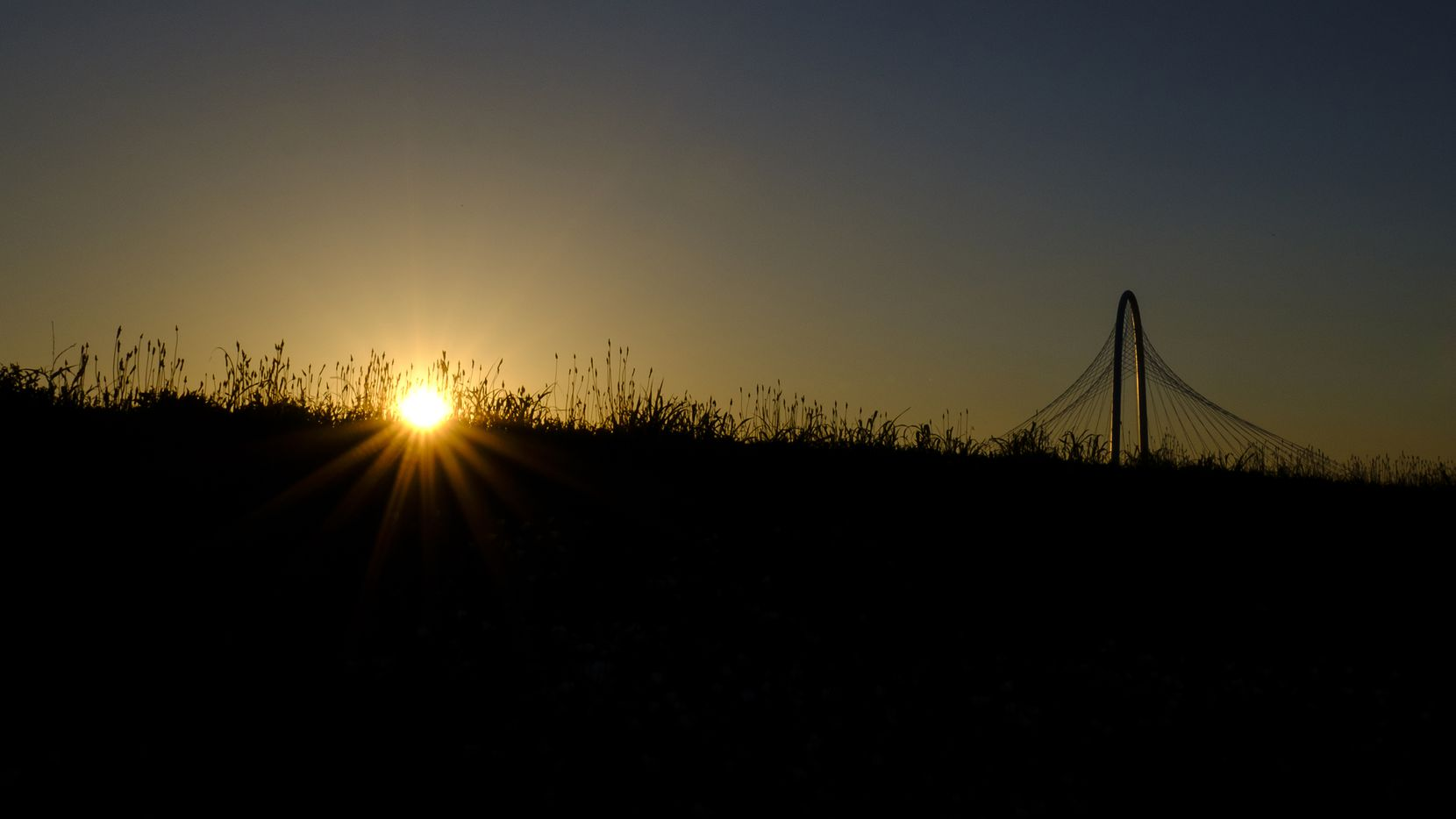 The sun setting behind the Margaret Hunt Hill Bridge on Wednesday, May 15, 2019, in Dallas.