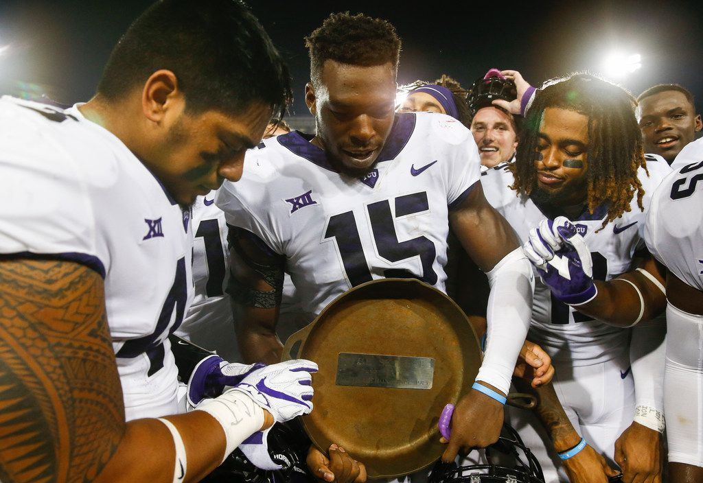"TCU teammates Ben Banogu (15), Izaih Filikitonga, left, and Jaelan Austin, right, celebrate with the ""Iron Skillet"" trophy following their teams win over SMU during an NCAA college football game Friday, Sept. 7, 2018, in Dallas. TCU won 42-12. (AP Photo/Jim Cowsert)"