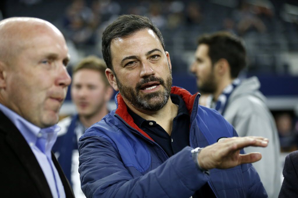 Television host Jimmy Kimmel talks with an unidentified person as he watches the Dallas Cowboys and the New York Jets warm up for an NFL football game, Saturday, Dec. 19, 2015, in Arlington, Texas.