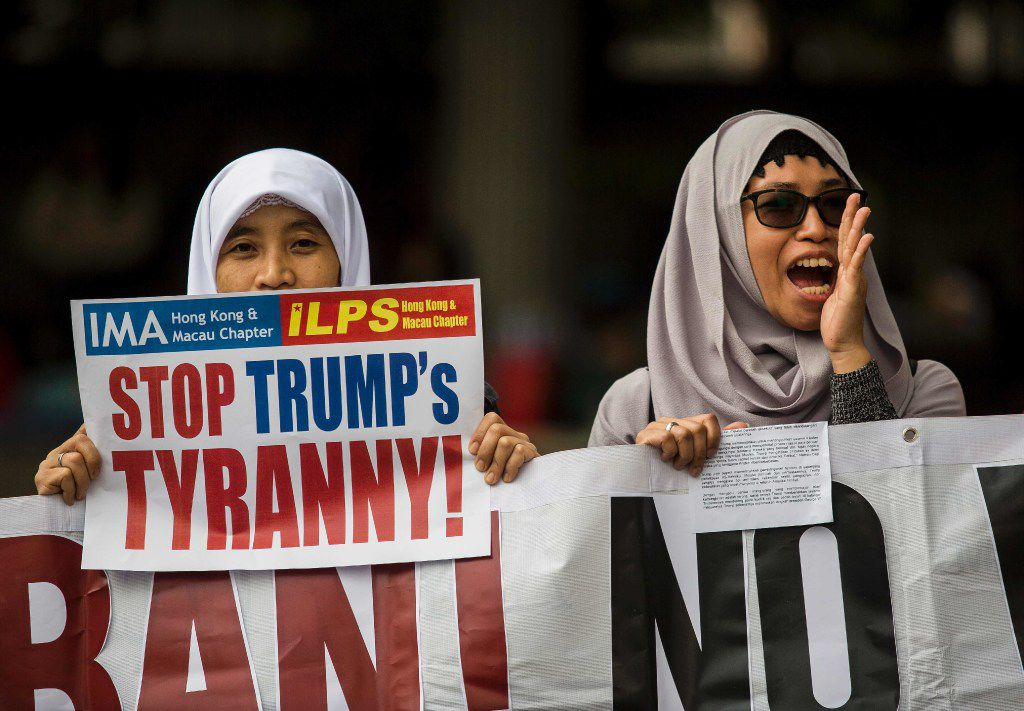 A protester (R) yells while another holds a placard during a rally organised by the International Migrants Alliance to protest against US President Donald Trump and his recent immigration and refugee restrictions, outside the US consulate in Hong Kong on February 5, 2017.