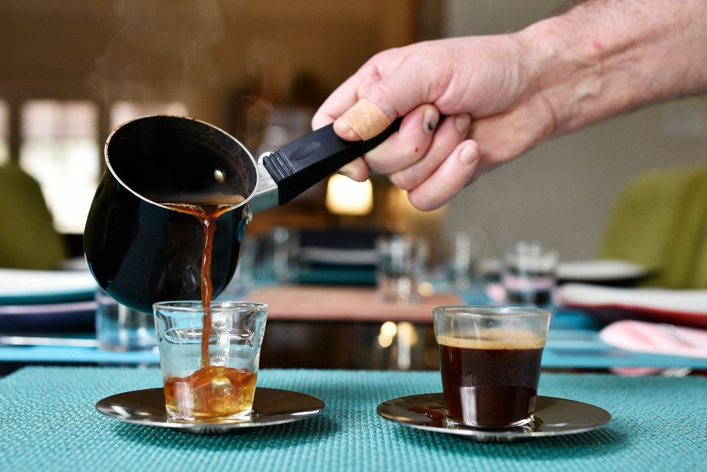 Israeli Chef Eldad Jacobson pours Turkish coffee. He adds hawaij after pouring.