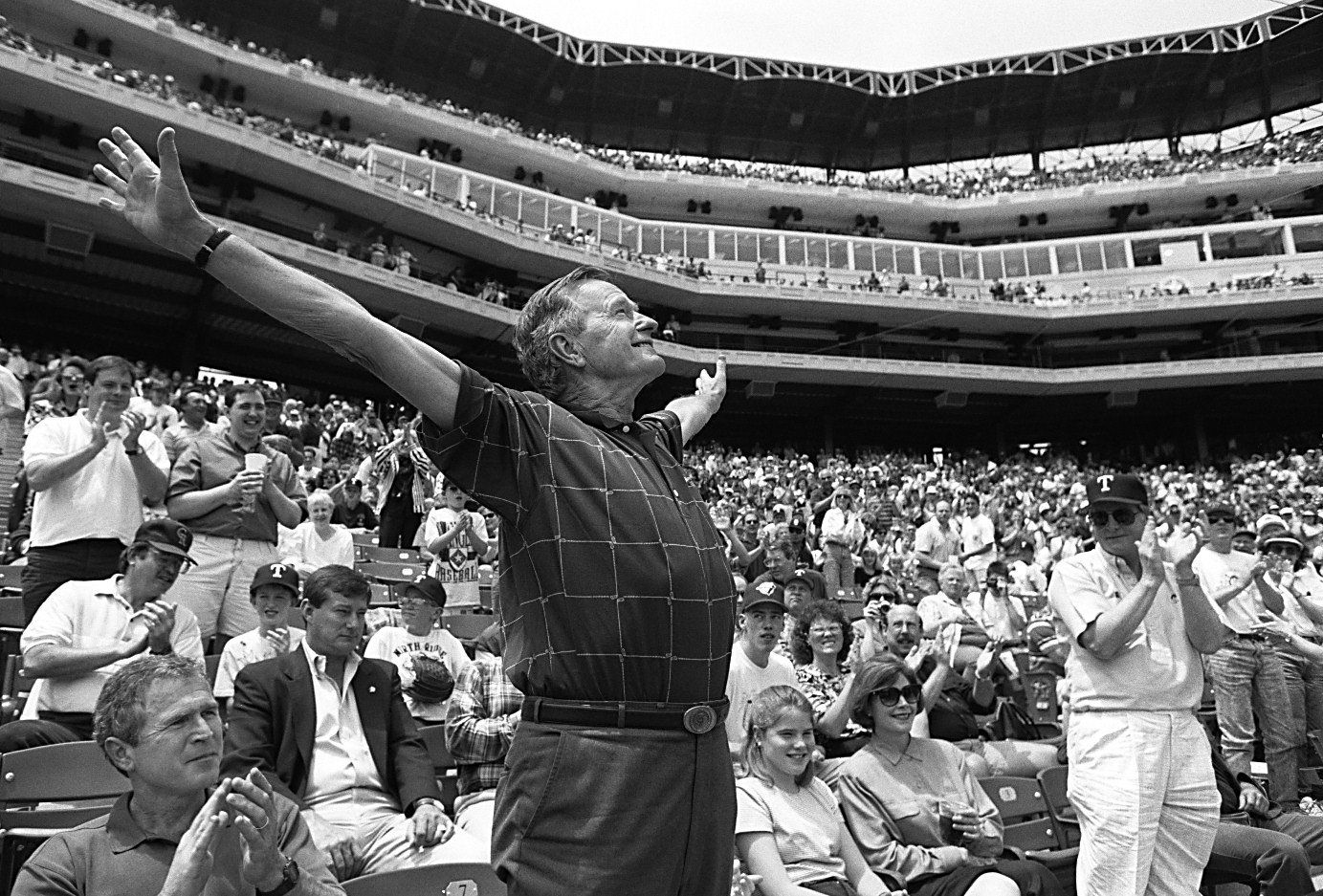 1994: Former Pres. George Bush acknowledges fans' cheers at The Ballpark in Arlington before the Texas Rangers played the Minnesota Twins. Son George W. Bush, Rangers' managing general partner, is seated at left, with wife Laura and daughter Jenna Bush at right.
