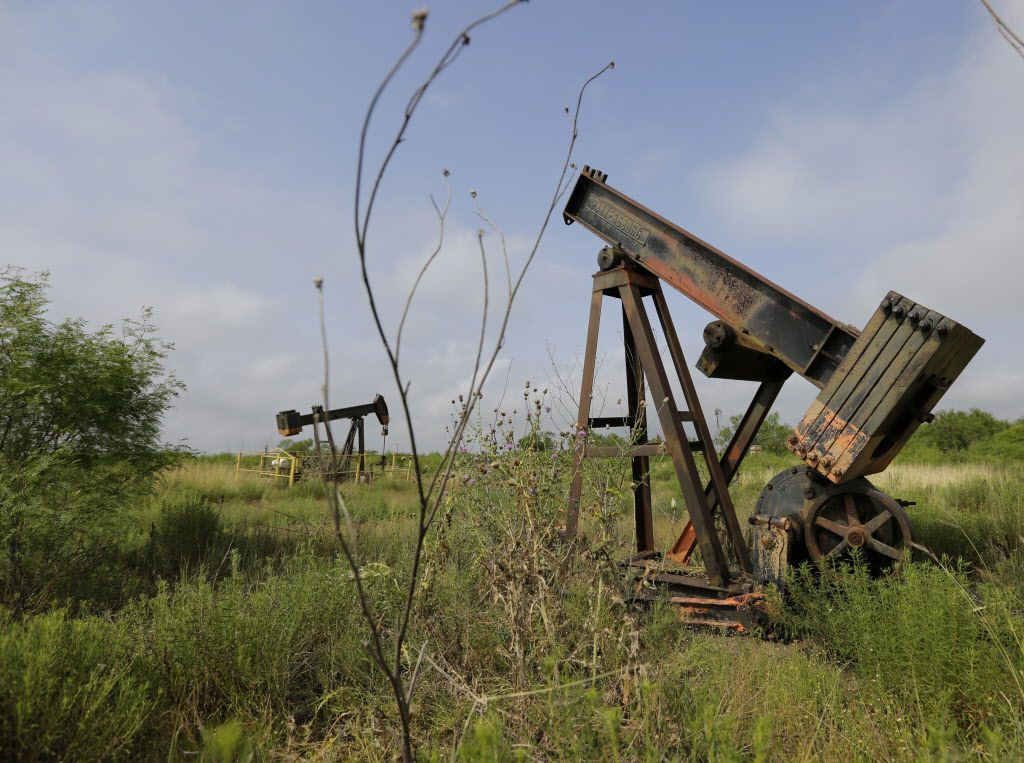 Pump jacks sit idle on a South Texas ranch near Bigfoot. Deserted drilling wells are the relics of every oil bust, and Texas is pitted with more than any other place in the U.S.