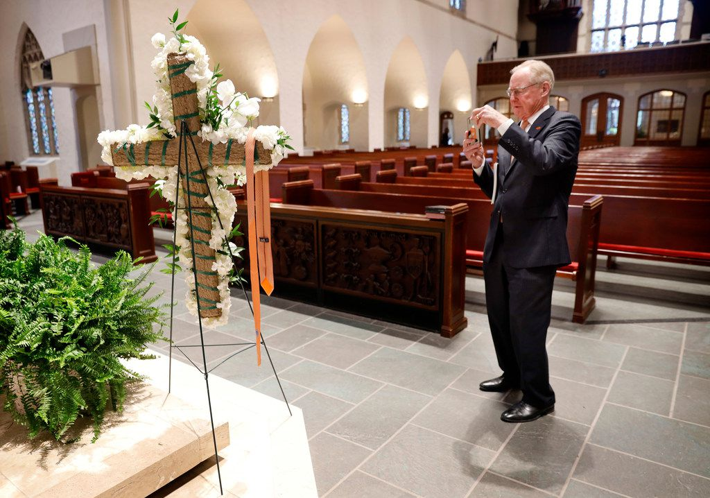 Oklahoma State University President V. Burns Hargis takes a photo of an OSU tie draped over a white floral bouquet after the funeral service for T. Boone Pickens.. Longtime friend Alan White removed his tie following his remarks and draped it over the cross.