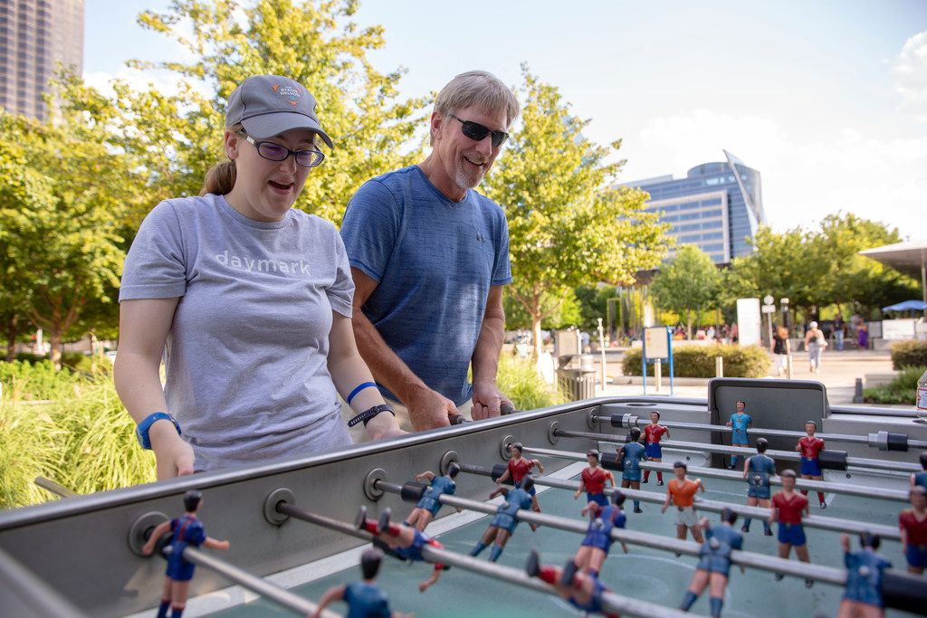 Katie Boone (left) plays foosball with Bob Waterman (right) at Klyde Warren Park in Dallas, Texas, Saturday, June 16, 2018. Daymark Living's Social Club creates opportunities for adults with intellectual and developmental delays ages 16  and older to participate in activities together promoting peer interaction. The special needs community will open soon in Waxahachie. (Allison Slomowitz/ Special Contributor)