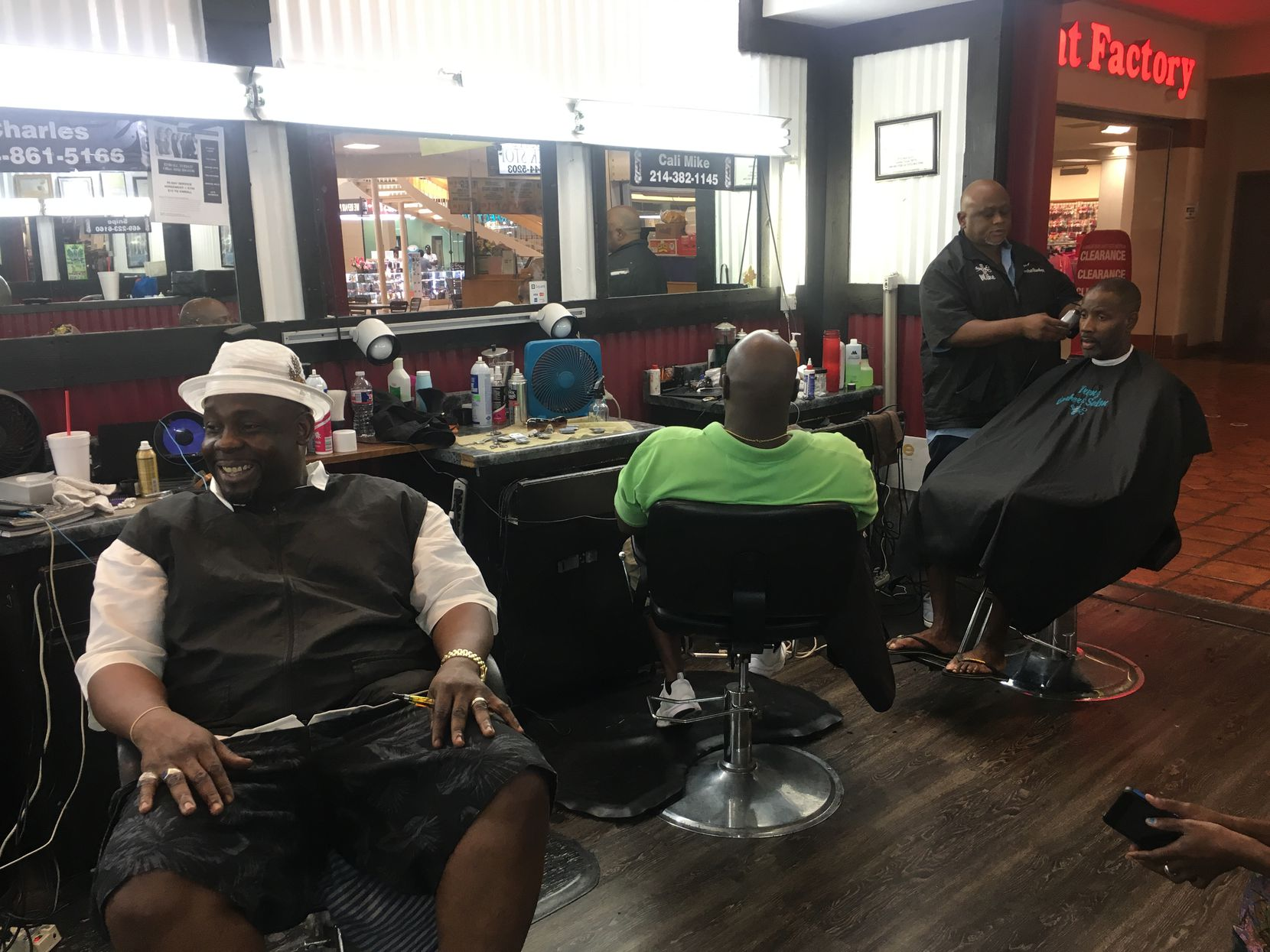 Men hang out at Trendz Barber Shop in Southwest Center Mall, discussing Thursday's protest that turned violent.