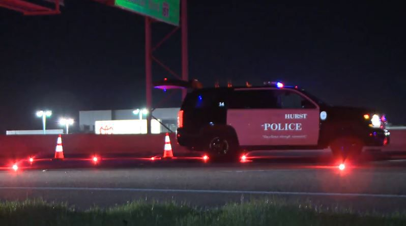 A Hurst police vehicle helps block traffic along Interstate 820 after a woman running in the road was struck and killed.