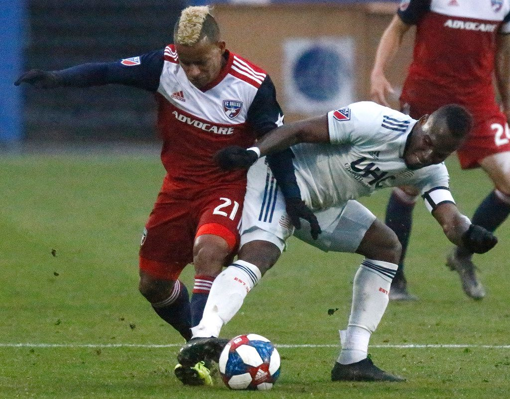 New England Revolution forward Cristian Penilla (70) slides into FC Dallas midfielder Michael Barrios (21) during the second half as FC Dallas hosted New England Revolution at Toyota Stadium in Frisco on Saturday, March 2, 2019.  (Stewart F. House/Special Contributor)