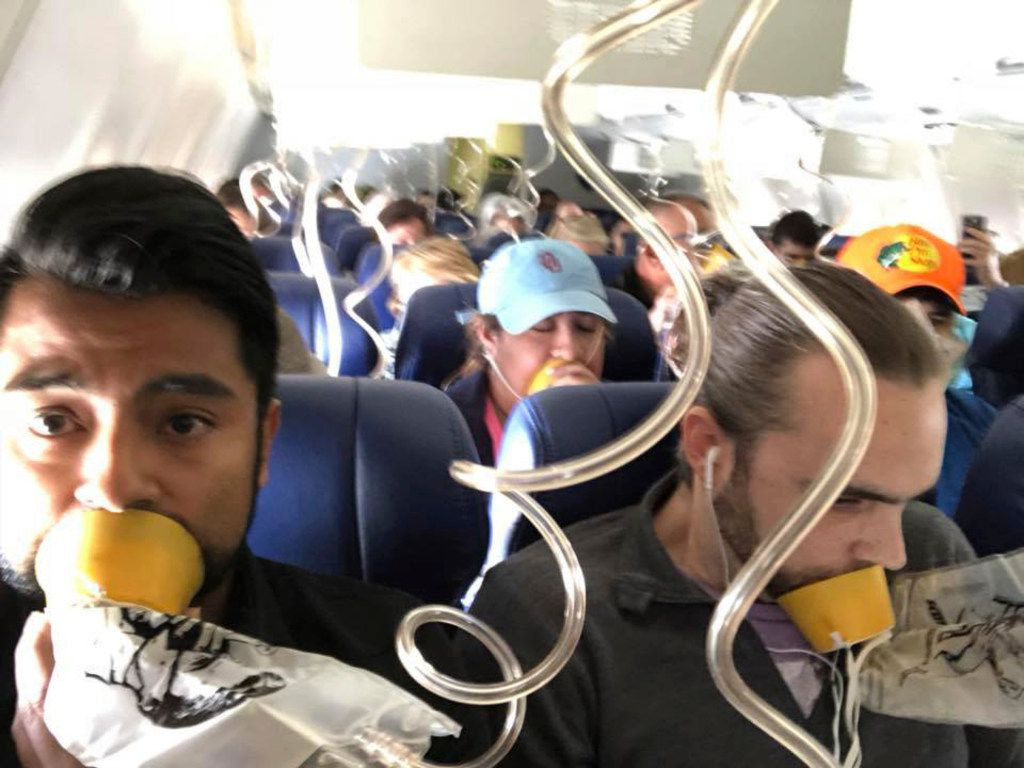 In this April 17, 2018 photo provided by Marty Martinez, Martinez, left, appears with other passengers after a jet engine blew out on the Southwest Airlines Boeing 737 plane he was flying in from New York to Dallas. (Marty Martinez via AP)