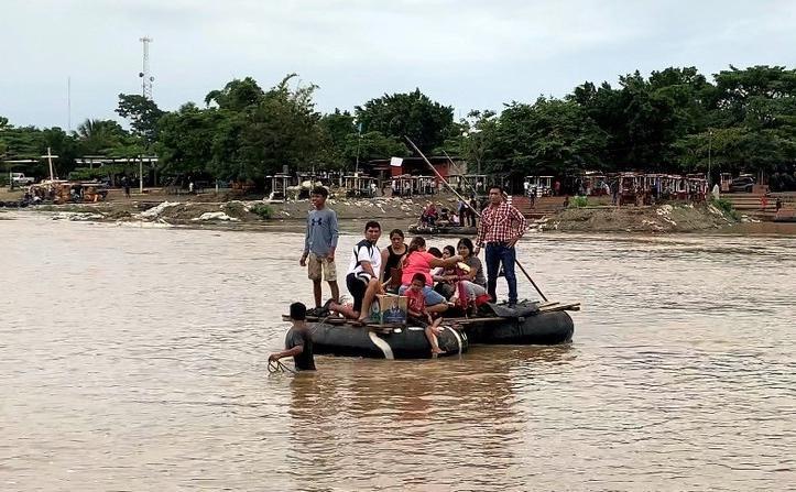 Un grupo de personas cruzan en una balsa el Río Suchiate entre Chiapas, México y Guatemala.(AGENCIA REFORMA)