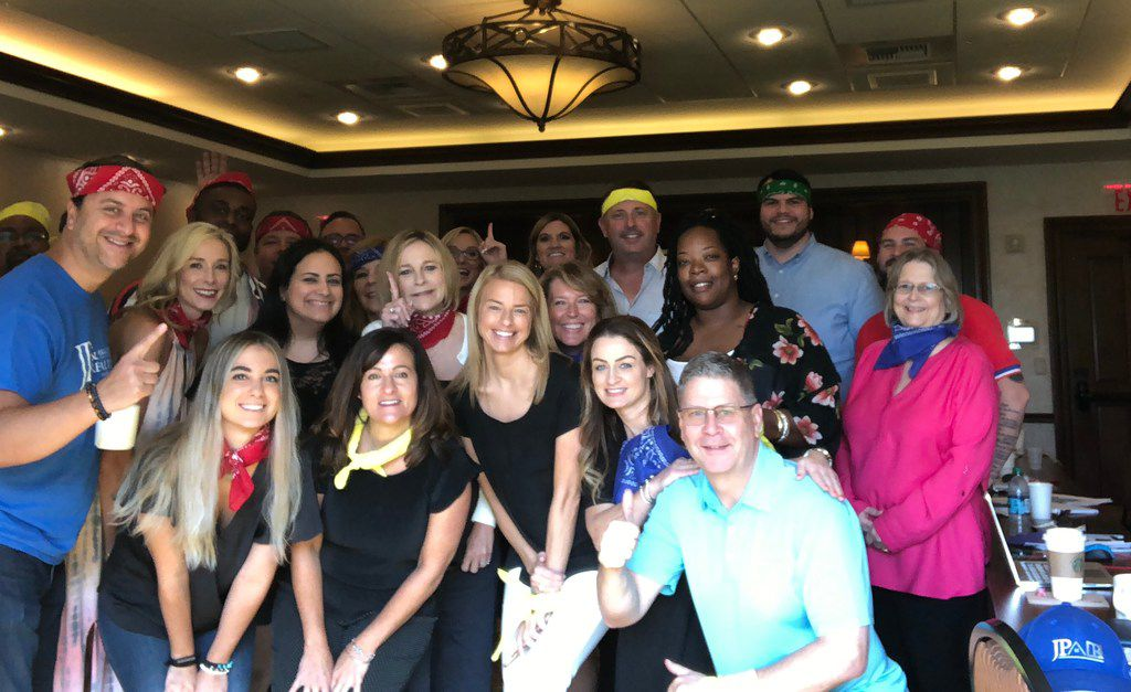 JP Piccinini (in the red bandana at left) is shown with staff members at JP & Associates Realtors' summer retreat at the Gaylord Texan. Piccinini's red bandana means action-driven,  he says.