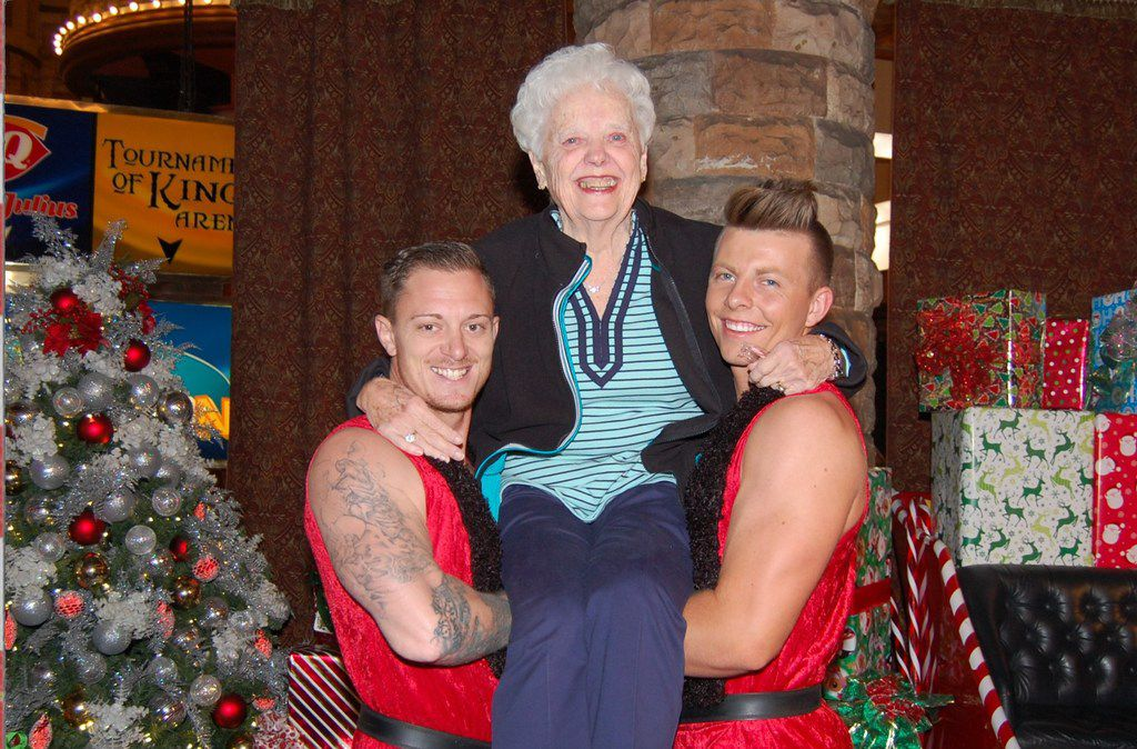 """Two dancers from the """"Thunder From Down Under"""" show in Las Vegas held Barbara Cannizzaro in November 2016 during a three-generation visit with her two daughters and a niece. The photo ended up on her Christmas card that year."""
