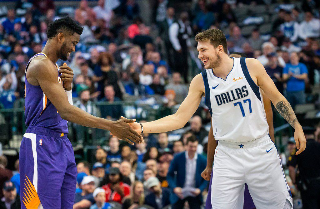 Dallas Mavericks forward Luka Doncic (77) shakes hands with Phoenix Suns center Deandre Ayton (22) as they take the floor before an NBA basketball game at American Airlines Center on Wednesday, Jan. 9, 2019, in Dallas. (Smiley N. Pool/The Dallas Morning News)
