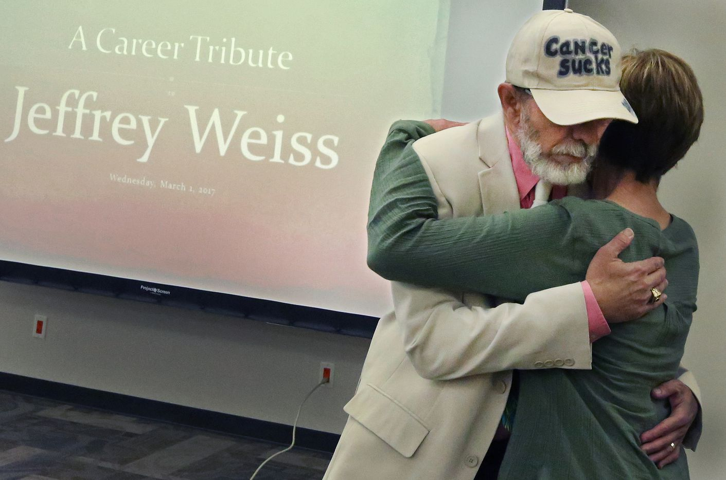 Jeffrey Weiss gets a hug from co-worker Sharon Grigsby at his career tribute party at The Dallas Morning News on Wednesday, March 1, 2017. (Louis DeLuca/The Dallas Morning News)