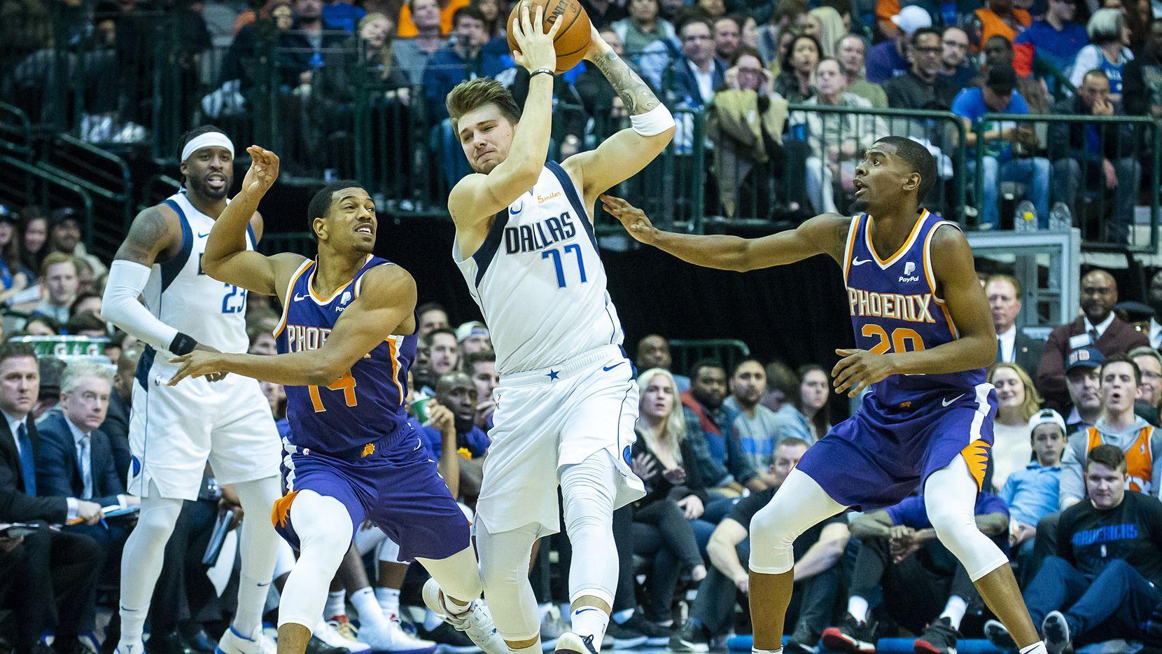 El delantero de los Mavericks de Dallas, Luka Doncic (77) defiende el balón ante la marca de De'Anthony Melton (14) y Josh Jackson (20) de los Suns de Phoenix. (Smiley N. Pool/The Dallas Morning News)