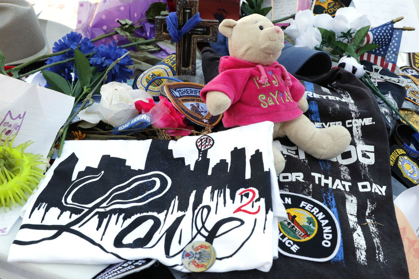 Two Dallas police patrol cars are covered with notes, flowers, balloons and other items as part of a makeshift memorial at the Jack Evans Police Headquarters on Monday, July 18, 2016.