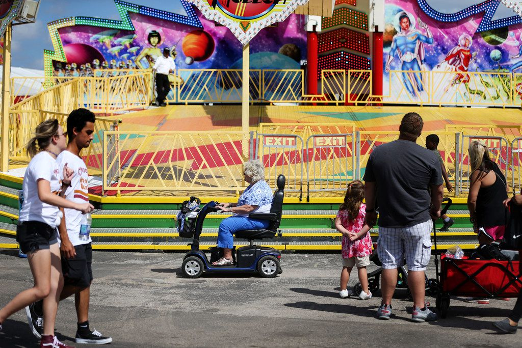 A woman drives her scooter past a ride at the State Fair of Texas at Fair Park in Dallas on senior citizen day, Thursday, Oct. 4, 2018.