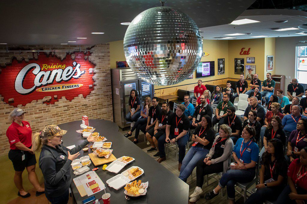 """Dominique Vitry (bottom left) leads a training for how to """"build The Perfect Box"""" beneath a disco ball at Raising Cane's offices on in Plano."""
