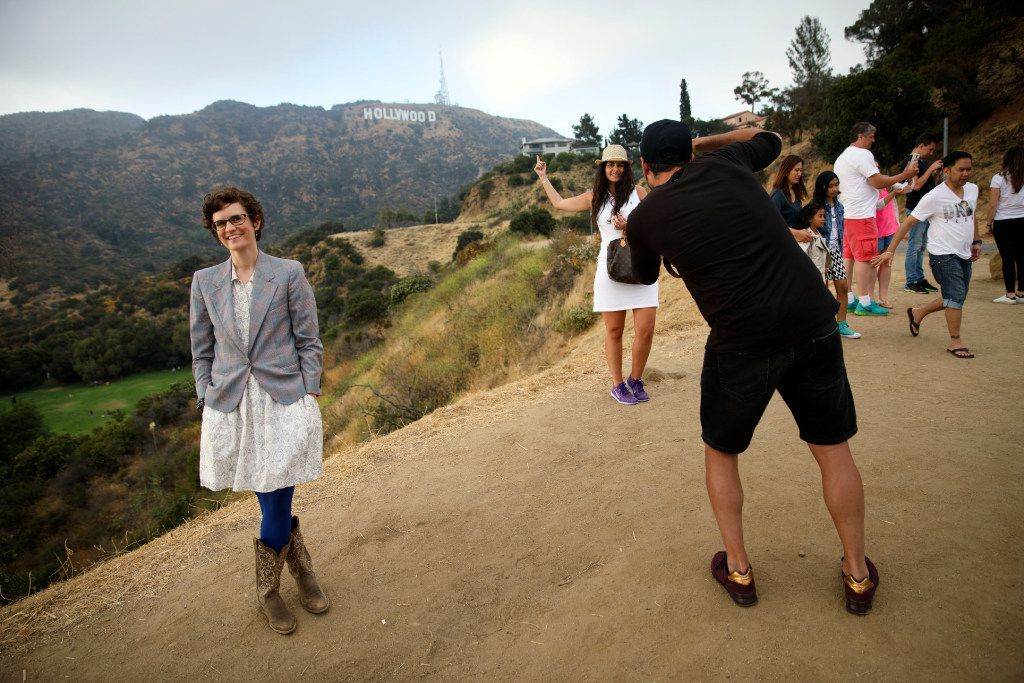 Author Merritt Tierce poses for a portrait next to tourists taking pictures near the Hollywood sign.