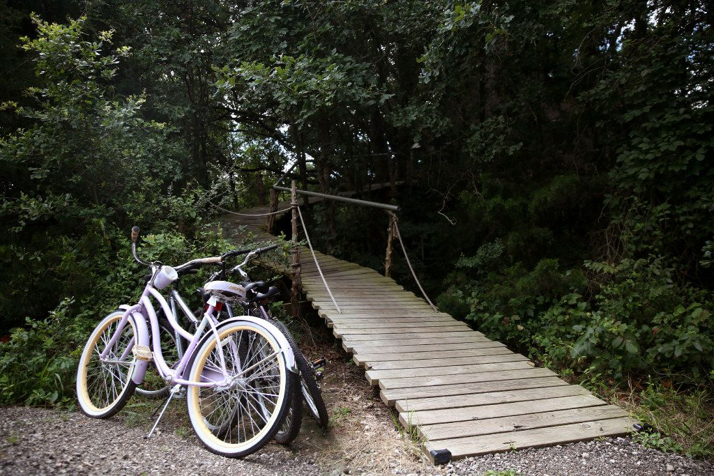 Bicycles are parked by the walkway leading to the Bare Creek Treehouse at Savannah's Meadow