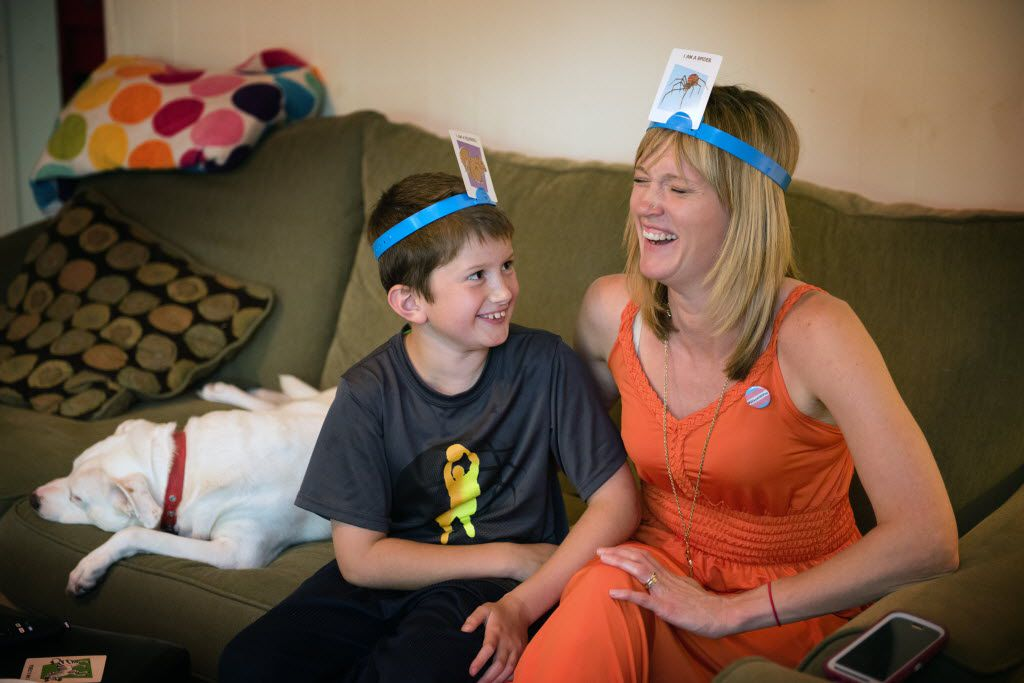 Max Briggle and Amber Briggle laugh during a family game in their Denton home on May 15, 2016.