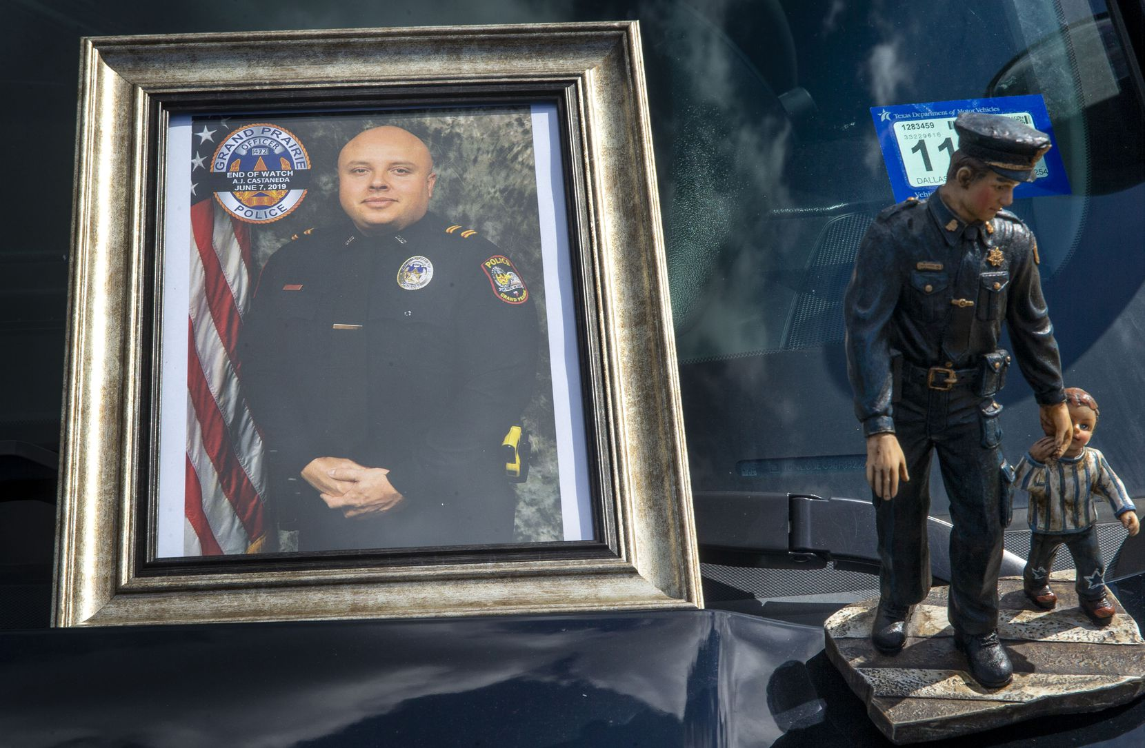 "A photograph of Grand Prairie Police Officer Albert ""A.J."" Castaneda and a statue adorn the hood of a police vehicle at the Grand Prairie Police Department in Grand Prairie, TX, on Friday, June 7, 2019. Castaneda was struck and killed by a vehicle as he ran traffic enforcement Friday morning. (Lynda M. Gonzalez/The Dallas Morning News)"
