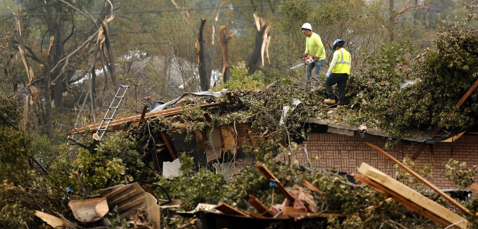 Workers cut up and remove a tree that toppled onto a home on Royal Lane in northwest Dallas.
