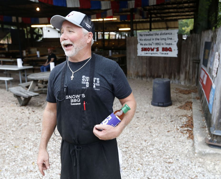 Owner Kerry Bexley prepares to give away a koozie and a bottle of barbecue sauce to a random person waiting in line at Snow's BBQ.
