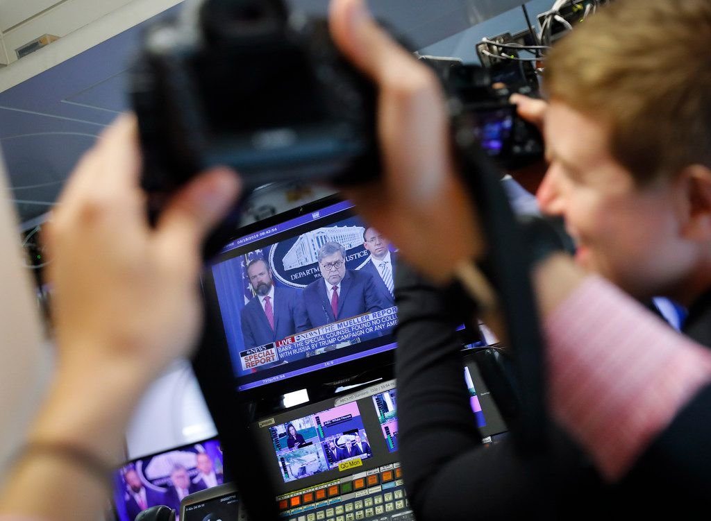 Journalists take photographs of the television broadcast monitors in the press room of the White House of Attorney General William Barr speaking alongside Deputy Attorney General Rod Rosenstein (right) and Deputy Attorney General Ed O'Callaghan, about the release of a redacted version of special counsel Robert Mueller's report.