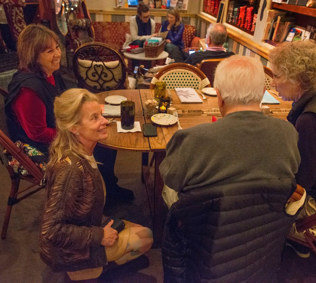Hedda Dowd kneels to chat with a table of long-time regulars in her Inwood Village restaurant Rise Soufflé Salon in Dallas, Texas on December 20, 2017. (Robert W. Hart/Special Contributor)