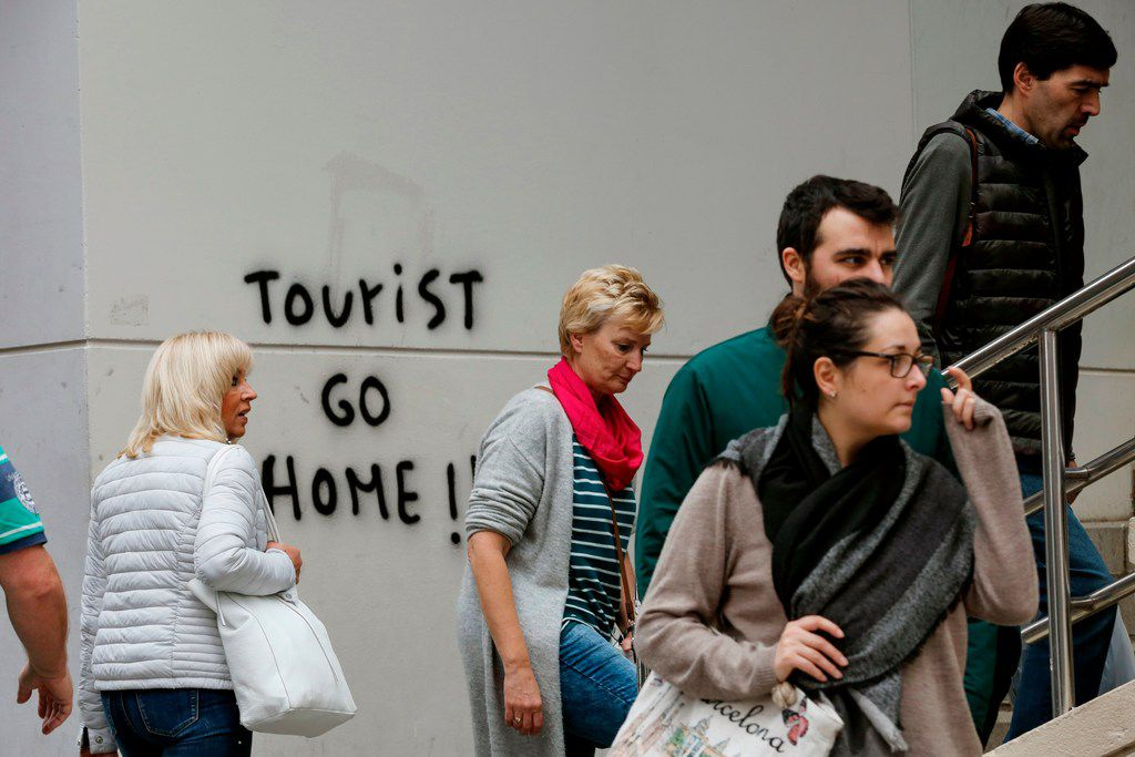 """Visitors  walked past graffiti reading """"Tourist go home!"""" on their way to Park Guell in Barcelona in November."""