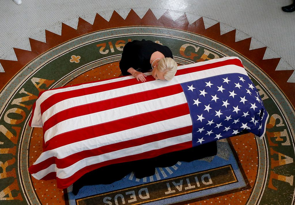 Cindy McCain, wife of the late Sen. John McCain, touches her husband's coffin during his memorial service in the museum rotunda at the State Capitol in Phoenix, Aug. 29, 2018.
