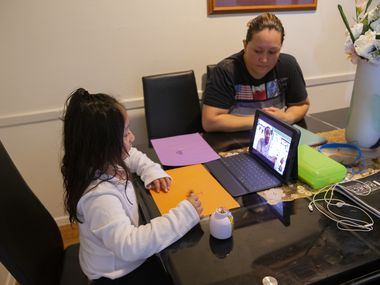 Adali Arriaza (right) watches as her daughter Daysha Cojulum, 5, attends her virtual class at the kitchen table on Sept. 16, 2020 in Northwest Dallas. Cojulum uses her mother's phone to connect to the internet due to the DISD hotspots not working properly or running out of the allotted data. (Juan Figueroa/ The Dallas Morning News)