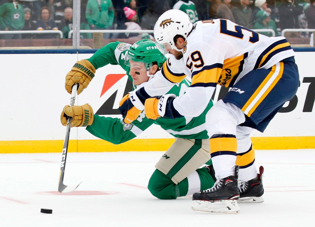 Dallas Stars left wing Roope Hintz (24) passes the puck as he's taken down by Nashville Predators defenseman Roman Josi (59) during the third period of the NHL Winter Classic hockey game at the Cotton Bowl in Dallas, Wednesday, January 1, 2020. The Stars came back to win, 4-2. (Tom Fox/The Dallas Morning News)