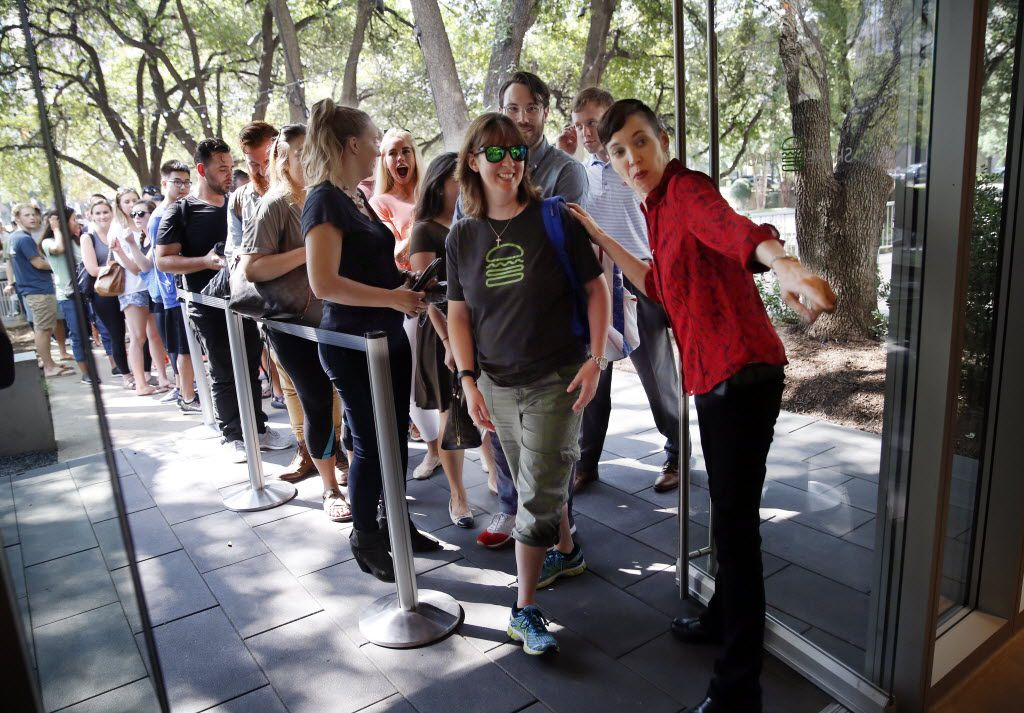 First customer Marisa Martinez (center) of Garland is shown where to order a burger after the doors opened at Dallas' first Shake Shack.