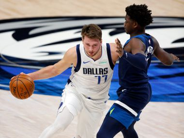 Mavericks guard Luka Doncic (77) drives on Timberwolves guard Anthony Edwards during the first quarter of a preseason game at American Airlines Center in Dallas on Thursday, Dec. 17, 2020.