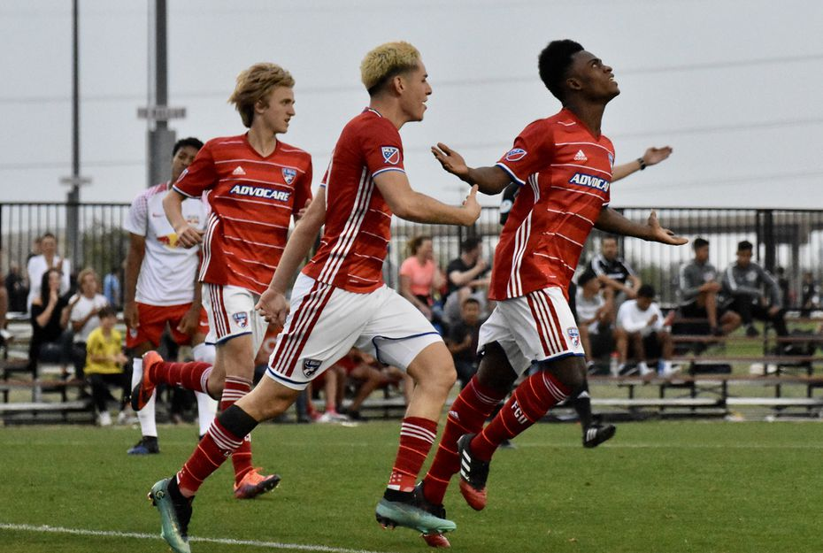 Ronaldo Damus (right) celebrates a goal in the 2018 Dallas Cup against Red Bull Brasil along with Brayan Padilla (center) and Thomas Roberts (left).